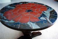 This table, 40 inches in diameter, features a large cut mosaic of a poppy blossom.