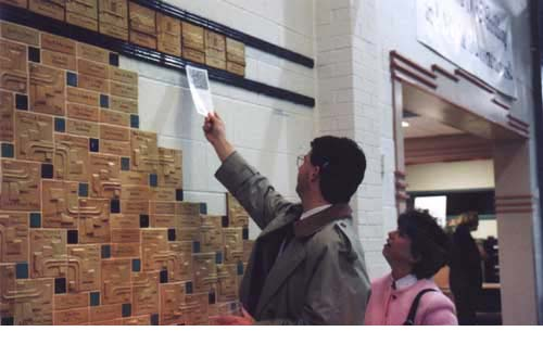 Donors locate their tile on the wall during a fundraising event.